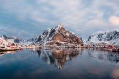 Mountain reflection on arctic ocean with norwegian fishing villa. Ge at Reine, Lofoten island, Norway royalty free stock photos