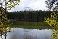 Mountain reflection in a calm lake during fall hike Stock Images