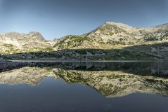 Mountain reflection in a huge alpine lake. In Retezat Mountains, Romania Royalty Free Stock Photo