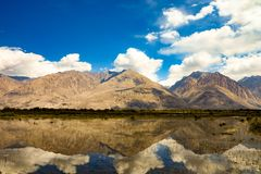 Mountain reflection. Mountain reflecton on water and blue sky with beautiful white cloud stock photos