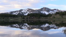 Mountain Reflection at Sunrise in Lake. A scenic reflection of the Colorado mountains in summer stock video footage
