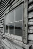 Mountain reflection in window, Okarito, NZ Royalty Free Stock Images