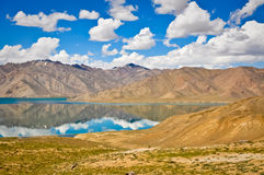 Mountain Reflections in Tajikistan. The crystal clear waters of Bulunkul Lake in Tajikstan reflect the barren mountains, sky and clouds on a summer afternoon Royalty Free Stock Photography