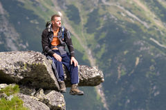 Mountain relaxation. Young men is relaxing on the edge of precipice in Tatra Mountains, Slovakia Stock Image