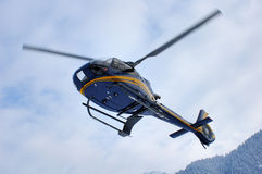 Mountain rescue. A helicopter coming in to land in the snowy mountains. Motion blur on the blades Stock Photo