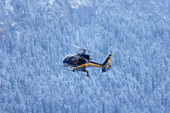Mountain rescue. A mountain rescue helicopter coming in to land against a backdrop of snowy mountain forest Royalty Free Stock Photo