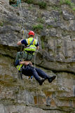 Mountain rescue. Man being rescued off a high mountain cliff face royalty free stock photo