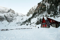 Mountain Rescue Chalet on a valley, surrounded by mountains. Beautiful landscape of a Mountain Rescue chalet on a valley, surrounded by mountains, during winter Royalty Free Stock Images