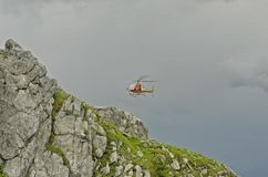 Mountain rescue. A helicopter of the Mountain rescue in action on the Alps of Monte Pal Piccolo (Kleiner Pal Stock Photography