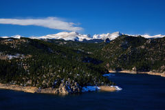 Mountain Reservoir with Snow Covered Peaks and Pine Trees Stock Image