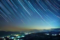 Mountain resort under star trails Stock Photo