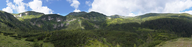 Mountain ridge. Mountain panorama view with juniper forest and snow remains on ridge in distance. Five shots stitch image Royalty Free Stock Photo