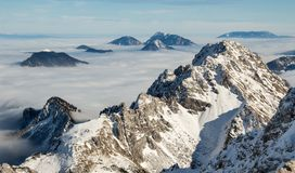 Mountain ridge above the clouds. Mountain chain covered in snow above clouds Stock Images