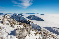 Mountain ridge above the clouds. Mountain chain covered in snow above the clouds Stock Photo
