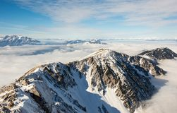 Mountain ridge above the clouds. Mountain ridge covered in snow above the clouds Royalty Free Stock Photo