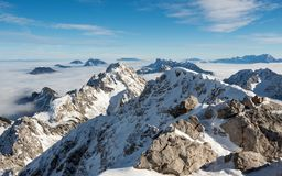 Mountain ridge above the clouds. Mountain ridge covered in snow above the clouds Royalty Free Stock Photography