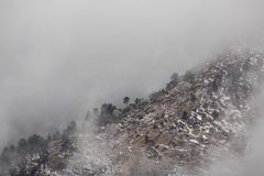 Mountain ridge appearing through the fog on a winter day. A mountain ridge appears through the fog on a cold winter day Royalty Free Stock Image