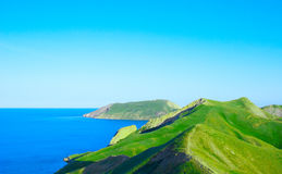 Mountain ridge and blue sea Royalty Free Stock Images