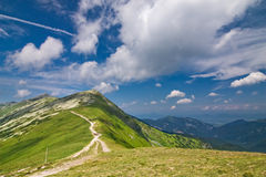 Mountain ridge and blue sky with clouds Stock Image