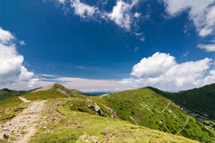 Mountain ridge and blue sky with clouds Stock Photo