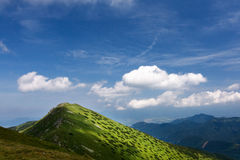 Mountain ridge and blue sky with clouds Royalty Free Stock Photos