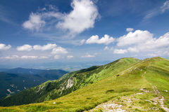 Mountain ridge and blue sky with clouds Stock Photos