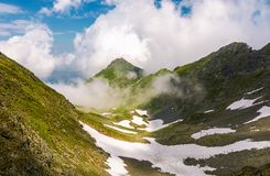 Mountain ridge among the clouds. Beautiful summer landscape with peak in the far distance Royalty Free Stock Image