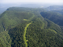 The mountain ridge covered forest. The road in the forest. Mount Stock Image