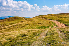 Mountain ridge dirt road  under the clouds. Lovely early autumn scenery in fine weather Stock Photos
