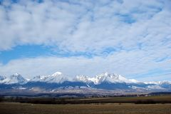 Mountain ridge High Tatras. Slovakia. Panorama of the cloudy blue winter sky above the snow-capped peaks of the High Tatras. royalty free stock photography