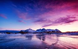 Mountain ridge and ice on the frozen lake surface. Natural landscape on the Lofoten islands, Norway. Water and mountains during sunset royalty free stock photo