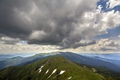 Mountain ridge landscape under dramatic cloudy sky, summer or spring wide panoramic view.  royalty free stock photos