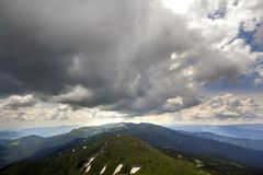Mountain ridge landscape under dramatic cloudy sky, summer or spring wide panoramic view.  royalty free stock image