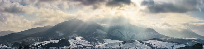 Mountain ridge in light beams on cloudy winter day. Gorgeous countryside panorama stock photo