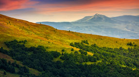 Mountain ridge with peak behind the hillside at sunset. Mountain ridge with peak behind the hillside. beautiful summer background at sunset with red sky Stock Photo