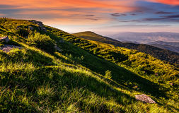 Mountain ridge with peak behind the hillside at sunset. Mountain ridge with peak behind the hillside. beautiful summer background at sunset with red sky Stock Photos