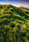 Mountain ridge with peak behind the hillside at sunset. Mountain ridge with peak behind the hillside. beautiful summer background at sunset with reddish sky Royalty Free Stock Photography