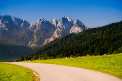 Mountain ridge and road in morning light. Mountain ridge, peaks and road in morning light in Austria, Dachstein area Stock Image