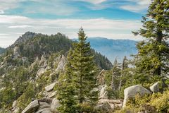 Mountain ridge with rocks and trees as well as mountains in the background. Pointy rocky ridge with trees and Grey boulders. In the background a mountain ridge royalty free stock photo