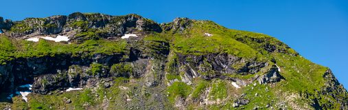 Mountain ridge with rocky cliffs and grassy slopes. Beautiful nature scenery of Fagaras mountains, Romania Stock Photography