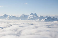 Mountain ridge sticking out of the clouds Royalty Free Stock Image