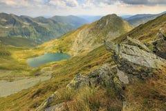 Mountain ridges and alpine lake,Capra lake,Fagaras mountains,Carpathians,Romania. Majestic lake in mountains and narrow ridges,Capra lake,Fagaras mountains Royalty Free Stock Image