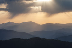 Mountain ridges at sunset against the sky with clouds Royalty Free Stock Images
