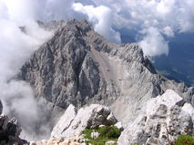 Mountain rising from clouds - Slovenian Alps. Jezerska Kocna viewed from Grintovec, Kamnik Alps, Slovenia, part of Southern Limestone Alps Royalty Free Stock Images