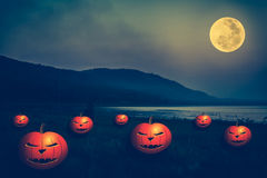 Mountain and river against blue sky and beautiful full moon at n. Background for Halloween holiday. Mountain and bright full moon at night. Pumpkins with scary Stock Images