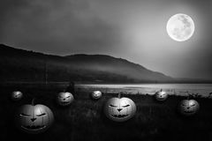 Mountain and river against blue sky and beautiful full moon at n. Background for Halloween holiday. Mountain and beautiful full moon at night.  Pumpkins with Royalty Free Stock Photography