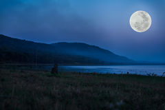 Mountain and river against blue sky and beautiful full moon at n Royalty Free Stock Image