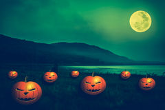 Mountain and river against blue sky and beautiful full moon. Mountain and beautiful full moon, outdoors at night.  Pumpkins with scary face on the riverbank Stock Image