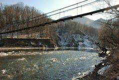 Suspension bridge over mountain river in Adygea Royalty Free Stock Photos