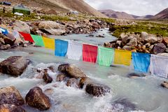 Mountain river and buddhist flags Stock Photography